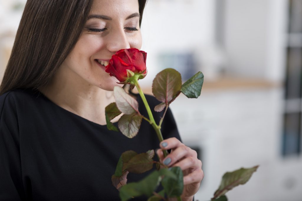A woman smelling a red rose